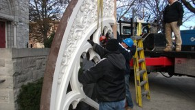 Preparing to hoist window frame into place.
